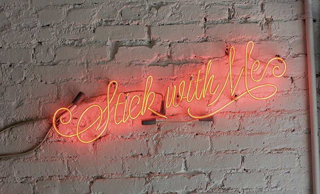 neon sign that says 'stick with me'