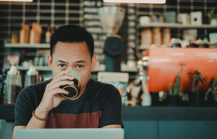 man drinking coffee while freelancing