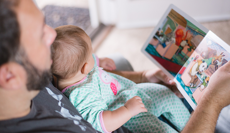 man reading a picture book to a baby